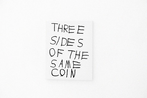 "A painting wuth the text ""three sides of the same coin"""