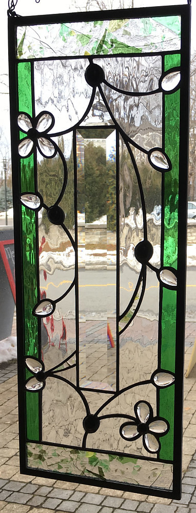 A stained glass panel in green and crystal colouration