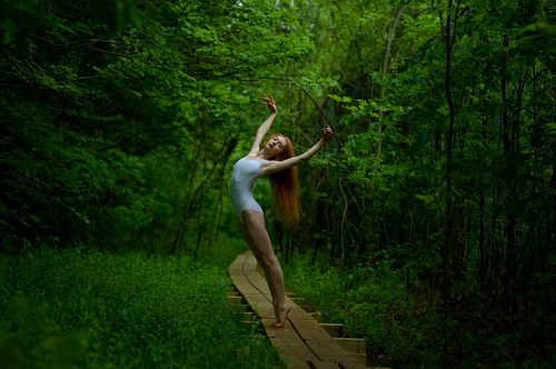 A photo of a ballerina dancing in the forest