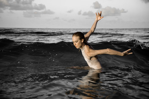 A photograph of a ballerina emerging from the ocean