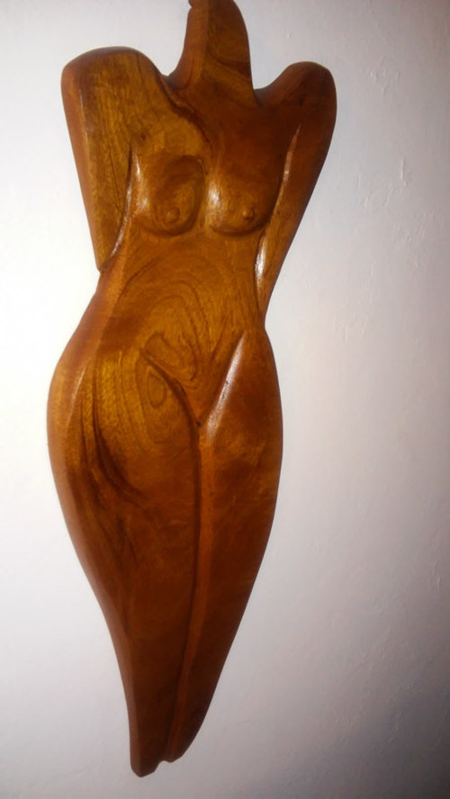 A sculpture of a female torso in wood