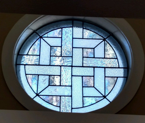 A stained glass window in the style of a Celtic weave