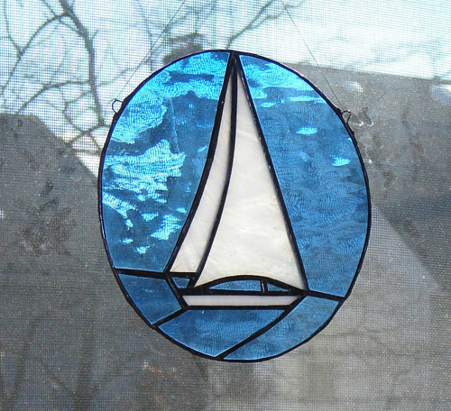 A small stained glass hanging depicting a sailboat