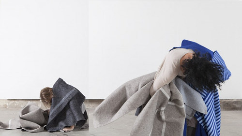 A photograph of two women curled up with large sheets of fabric
