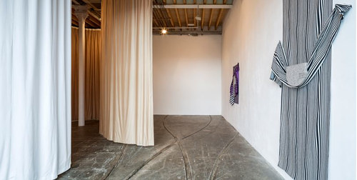 An installation view of an artwork with several dividing curtains