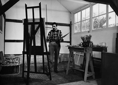 A photo of Arshile Gorky at work in his studio