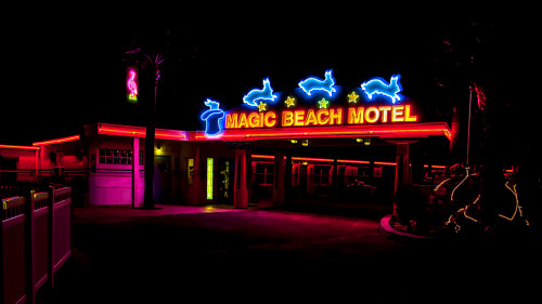 A photo of a neon motel sign at night