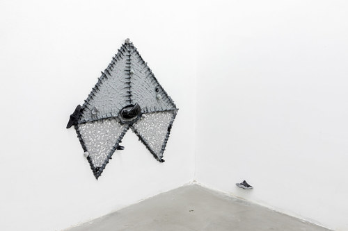 An art installation with a grey shape made from mixed sculptural media