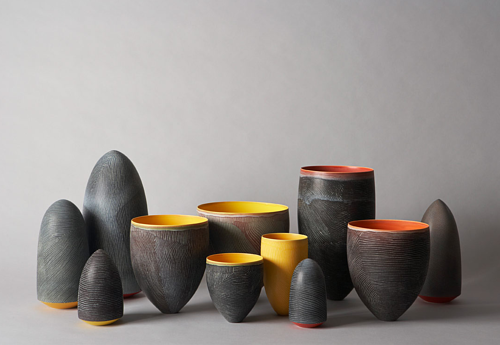 A group of ceramic vessels with neutral exteriors and coloured interiors