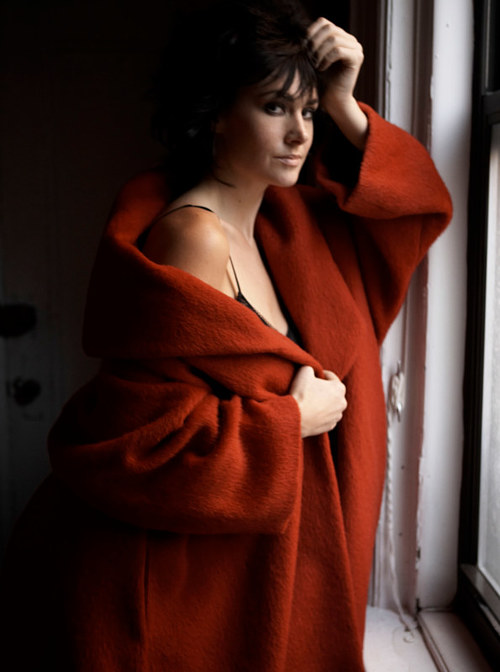 A photo of a woman standing in front of a window in a large red coat