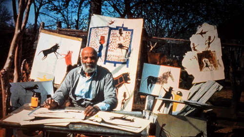 A photo of Bill Traylor surrounded by paintings in an outdoor space