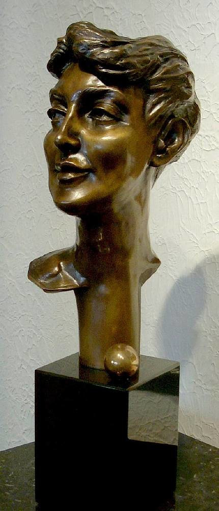 A bronze sculpture of a woman's face