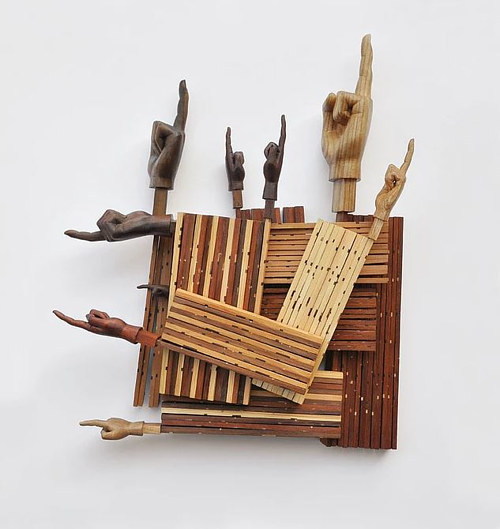 A sculptural installation with wood and carved hands