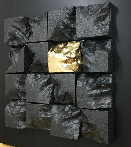 A sculpture made up of several square bricks sculpted like rocks