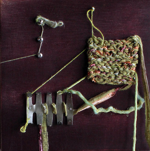 A mixed media assemblage with bits of metal, string, and wood