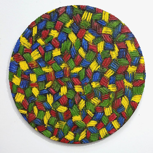 A circular wall-hanging artwork made up of paper clips and encaustic wax