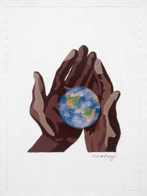 A textile artwork depicting the Earth in someone's hands