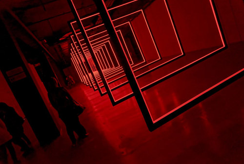 An installation view of a light-based artwork with deep red tones