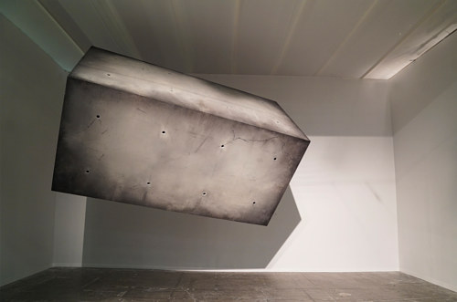 An installation consisting of a large concrete box suspended in a gallery