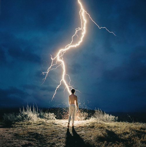 A photograph of a figure in front of striking lightning