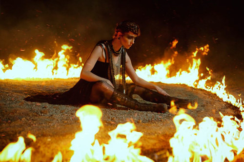 A photograph of a person sitting on the ground surrounded by flames