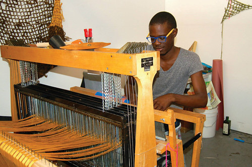 A photo of textile artist Diedrick Brackens working on his loom