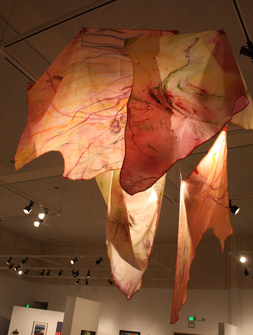A textile artwork hanging from the ceiling of a space