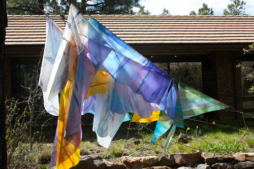 An outdoor installation with sheets of coloured fabric