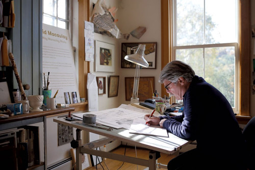 A photo of David Macaulay working in his studio
