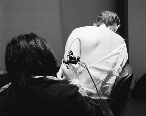 A photo of Juliana Barabas being tattooed as part of a performance