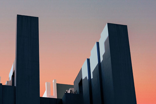 A photo of some monolithic buildings over a gradient sky