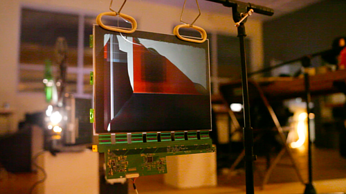 A still image from a performance involving the dismantling of an LCD screen
