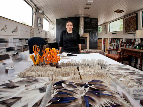 A photo of Kate MccGwire at work in her art studio