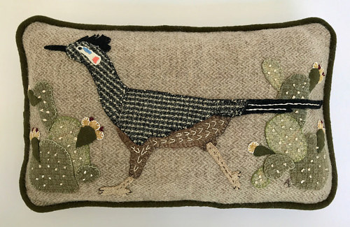 A wool applique pillow with a bird on it