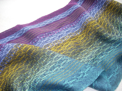 A handwoven shawl with purple fibres