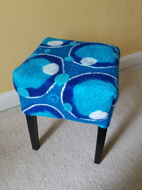 A hand-felted stool with a blue bubble pattern
