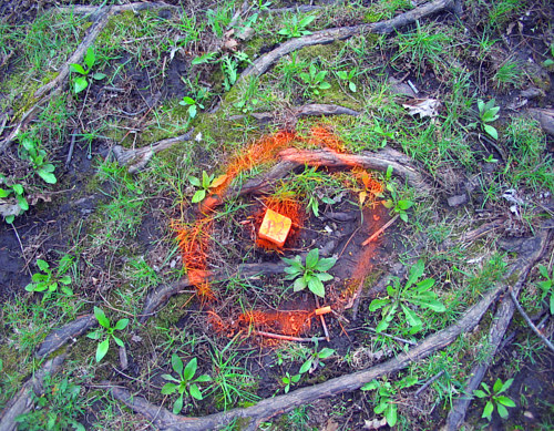 A photo of an orange spray paint circle on the ground