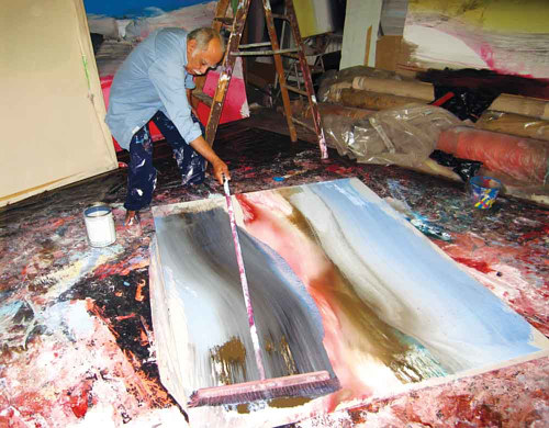 A photo of Ed Clark painting in his art studio