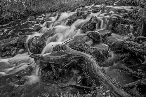 A black and white photograph of a flowing river
