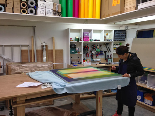 A photo of a studio assistant working at the atelier of Carlos Cruz-Diez