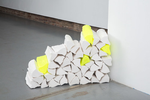 A sculptural artwork with pieces of cut wood painted white and neon