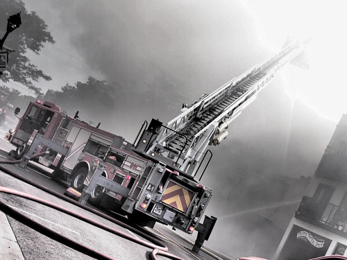 A photo of a fire truck with its ladder extending into the sky
