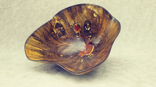 A sculpture with a bowl shape made from natural wood
