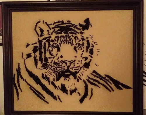 An image of a tiger made using coffee beans glued to a surface