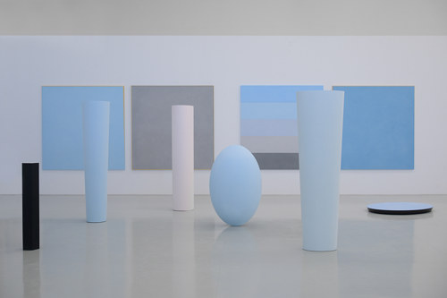 An installation view of several sculptural objects and monochrome paintings