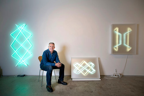 Photo of artist sitting next to his neon sculptures