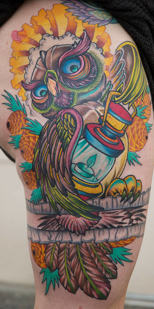 An owl and lantern leg tattoo in bright primary colours