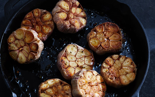A photo of roasted garlic in a cast iron pan