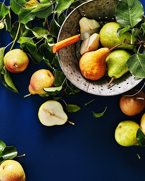 A photo of a bushel of pears on a deep blue table