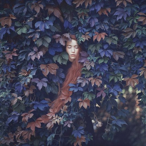 Photo of woman with long hair surrounded by leaves